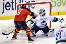 """Хоккеист """"Флориды"""" Стивен Вейсс пытается забросить шайбу в ворота """"Ванкувера"""" в матче НХЛ 9 января 2012 года. """"Флорида"""" одержала в понедельник первую победу над """"Ванкувером"""" в регулярном первенстве НХЛ более чем за 12 лет. REUTERS/Rhona Wise"""