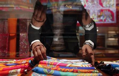 A saleswoman arranges scarves inside a Hermes showroom in Mumbai August 23, 2011. REUTERS/Danish Siddiqui/Files