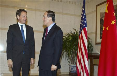 U.S. Treasury Secretary Timothy Geithner (L) chats with Chinese Vice Premier Wang Qishan before a dinner at the Diaoyutai State Guesthouse in Beijing, January 10, 2012. REUTERS/Andy Wong/Pool