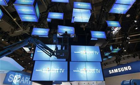 A worker on a lift aligns TVs and mirrors preparing the Samsung booth at the Consumer Electronics Show opening in Las Vegas January 9, 2012. REUTERS/Rick Wilking