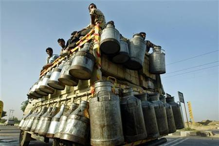 Indian milkmen sit on top of a truck with milk containers in New Delhi, October 4, 2005. REUTERS/Kamal Kishore