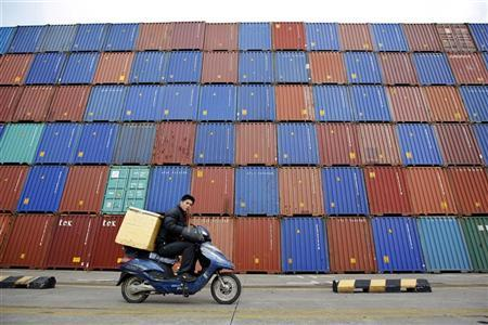 A man rides his motorcycle past shipping containers at the Port of Shanghai February 14, 2011. REUTERS/Aly Song