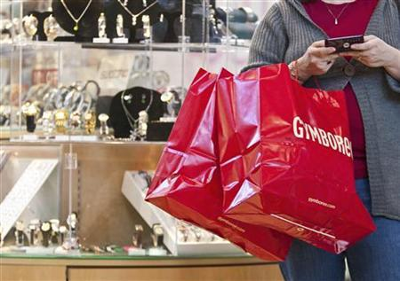 A woman uses a cell phone as she holds shopping bags at South Park mall in Charlotte, North Carolina November 25, 2011. REUTERS/Chris Keane