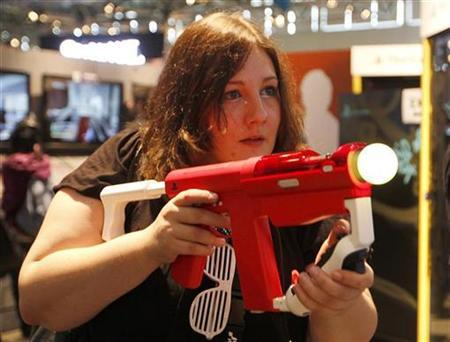 A visitor plays with a Playstation at the Sony Playstaytion exhibition stand during the Gamescom 2011 fair in Cologne August 18, 2011. REUTERS/Ina Fassbender