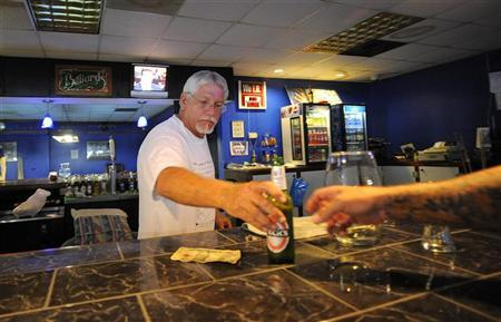 Business owner Stephen Gaughran (C) sells a beer to a regular customer from behind the bar inside his billiard hall in Titusville, Florida July 6, 2011. REUTERS/Brian Blanco