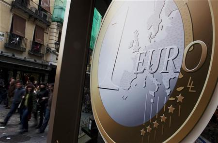 People walk past a pizza shop with a sign of a euro coin used to advertise its prices in central Madrid December 9, 2011. REUTERS/Susana Vera