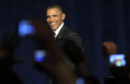 U.S. President Barack Obama smiles as he arrives on stage to speak at a campaign event in Washington January 9, 2012. REUTERS/Kevin Lamarque