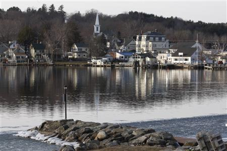Homes and businesses are reflected in the lake in Wolfeboro, New Hampshire January 9, 2012, where U.S. Republican presidential candidate and former Massachusetts Governor Mitt Romney owns an estate. REUTERS/Jessica Rinaldi