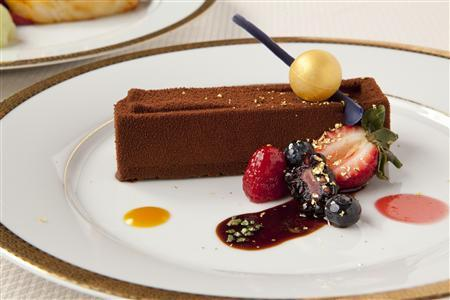 The dessert which will be served to guests attending the Hollywood Foreign Press Association's Golden Globe Awards on January 15, 2012, is pictured in this undated handout photograph. The Beverly Hilton's executive pastry chef Thomas Henzi will serve a chocolate almond crunch terrine with acacia honey, caramel and fresh berries. The chocolate will be flown in from Switzerland, while the acacia honey caramel will arrive from France, the Tarragon hazelnuts from Italy and the Valencia almond paste from Spain. Each desert plate will be sprinkled with 23-carat edible gold flakes along with a white chocolate ball sprayed with gold dust. REUTERS/Courtesy The Beverly Hilton/Handout