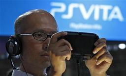 Посетитель выставки Tokyo Game Show в Тибе держит игровую приставку PlayStation Vita 15 сентября 2011 года. Отделение видеоигр Sony Corp должно сыграть ключевую роль в процессе возвращения компании к прибыльности. REUTERS/Kim Kyung-Hoon