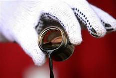 Президент Венесуэлы Уго Чавес держит емкость с нефтью с месторождения в поясе реки Ориноко 17 февраля 2008 года. Совместное предприятие ТНК-ВР и венесуэльской госкомпании PDVSA - PetroMonagas увеличит добычу высоковязкой нефти на 20 процентов в 2013 году - до 145.000 баррелей в сутки, пообещала ТНК- ВР. REUTERS/Miraflores Palace/Handout