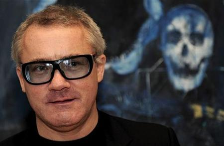 British artist Damien Hirst poses for photographers in front of his painting ''Shark's Jaw, Skull and Iguana on a Table'' (2008), in London October 13, 2009. REUTERS/Kieran Doherty