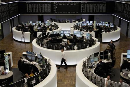 Traders are pictured at their desks in front of the DAX board at the Frankfurt stock exchange January 2, 2012.  REUTERS/Remote/Pawel Kopczynski