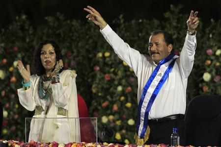 Nicaragua's President Daniel Ortega gestures to supporters while flanked by his wife Rosario Murillo after receiving the presidential sash during his swearing-in ceremony at the Revolution Square in Managua January 10, 2012. REUTERS/Oswaldo Rivas
