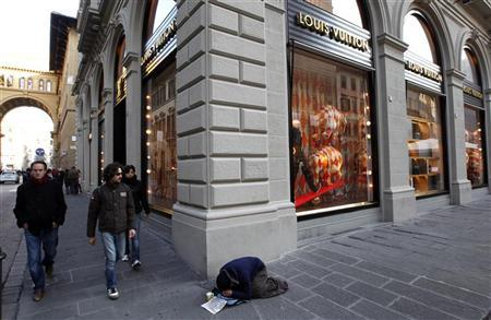 People walk past a beggar in front of a Louis Vuitton shop in downtown Florence November 20,2011.  REUTERS/Giampiero Sposito