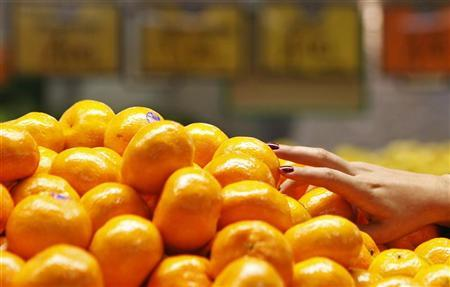 A woman picks up some mandarin oranges at a fruits shop in Sydney June 7, 2011. REUTERS/Daniel Munoz