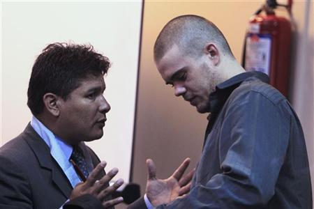 Dutch citizen Joran Van der Sloot (R) speaks to his lawyer Luis Jimenez at the end of his trial at the Lurigancho prison in Lima January 6, 2012.REUTERS/Pilar Olivares