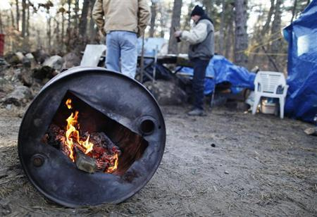 Two men talk while warming themselves by a fire in a homeless community near Lakewood, New Jersey January 9, 2012.   REUTERS/Lucas Jackson