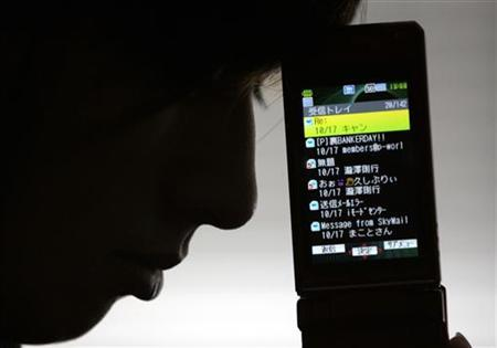Makoto, who requested that his last name not be used, poses for a photograph as he looks at his cell phone which became an instrument of mental torture that nearly drove him to suicide when he was a high school student in Tokyo October 22, 2007. REUTERS/Yuriko Nakao