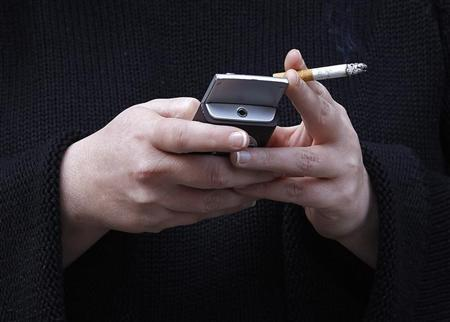 A woman uses her mobile phone while holding a cigarette in London in this February 1, 2010 file photo.  REUTERS/Suzanne Plunkett