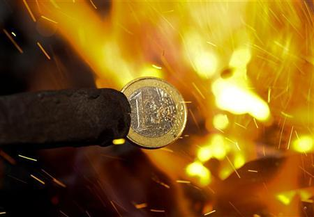 An illustration picture shows a one Euro coin being melted by a smith in Skopje, December 6, 2011. REUTERS/Ognen Teofilovski
