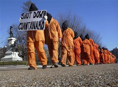 Members of the group ''Witness Against Torture'' dressed in orange prison jump suits protest against the detention camp at Guantanamo Bay, along Pennsylvania Avenue in Washington D.C. January 10, 2012.  REUTERS/Larry Downing