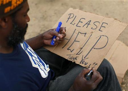 Homeless man Michael Long makes a sign on a piece of cardboard before walking out to a traffic intersection to ask for money from passing motorists in Pacific Beach, California January 11, 2012. REUTERS/Mike Blake
