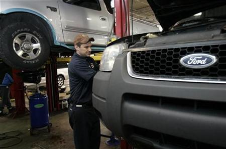 Auto mechanic Paul Cook works on a customer's Ford Escape SUV in the service department of a Ford car dealership in Warren, Michigan December 18, 2008. REUTERS/Rebecca Cook/Files