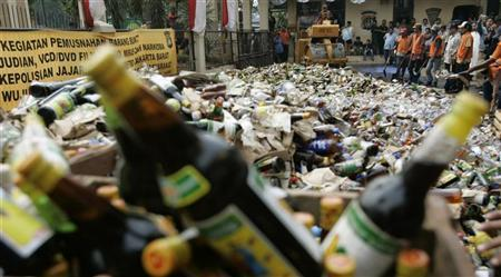 Officials destroy bottles of alcohol confiscated from street shops in Jakarta August 29, 2008. REUTERS/Supri