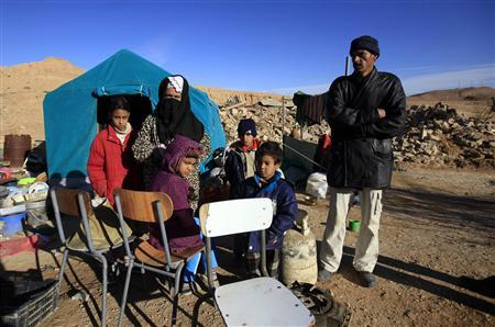 A family stands in front of their makeshift shack in the Algerian town of Laghouat January 11, 2012, where they have been living in for a week since their home was bulldozed as part of a government re-housing scheme. Most of their neighbours were re-housed in new apartments, but several families were not on the list for re-housing. REUTERS/Zohra Bensemra