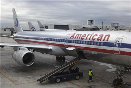 A worker walks underneath an American Airlines airplane at Miami International airport in Miami, November 29, 2011.   REUTERS/Lucas Jackson