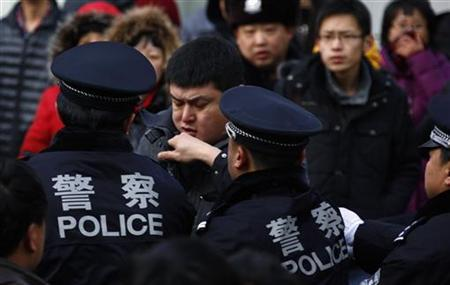 A man is dragged away by police after he refused to leave from the front of the Apple store in the Beijing district of Sanlitun January 13, 2012. REUTERS/David Gray