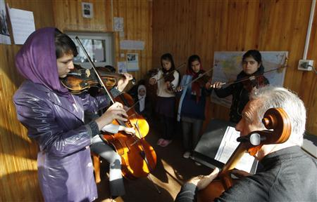 A teacher watches a female student playing the violin at the Kabul Music Academy January 7, 2012. In Afghanistan's sole music academy, students learn how to play traditional and western instruments as part of a government initiative to relieve the pains of decades of war through music. Despite a rich musical legacy, Afghanistan's melodic development has been severely disrupted by years of war and outright banned during the austere rule of the Taliban. At the Afghanistan National Institute of Music, orphans learn how to sing and play instruments alongside talented promising musicians who are selected on merit.  Picture taken January 7, 2012.  REUTERS/Omar Sobhani