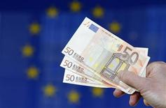 Человек держит в руке купюры валюты евро у штаб-квартиры Еврокомиссии в Брюсселе 28 ноября 2011 года. Евро растет к доллару после успешных долговых аукционов в Испании и Италии, а технические сигналы говорят о том, что он может также восстановиться против австралийского доллара. REUTERS/Francois Lenoir