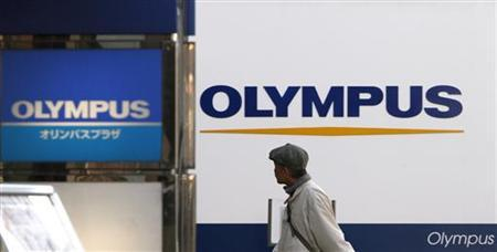 A man walks past signboards of Olympus Corp outside its showroom in Tokyo January 12, 2012. REUTERS/Toru Hanai