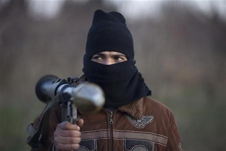 A Syrian soldier who defected to join the Free Syrian Army (FSA) carries a rocket-propelled grenade as he poses for a photograph at an FSA base outside the town of Qusair January 8, 2012. REUTERS/ Stringer