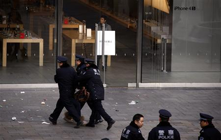 A woman is dragged away by police after she refused to leave from the front of the Apple store in the Beijing district of Sanlitun January 13, 2012. REUTERS/David Gray
