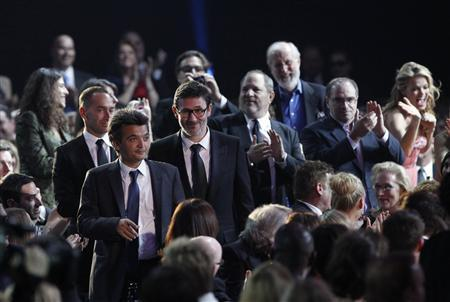 Producer Thomas Langmann (center L) and Director Michel Hazanavicius (C) walk to the stage to accept the best picture award for ''The Artist'' at the 17th Annual Critics' Choice Movie Awards in Los Angeles, January 12, 2012. REUTERS/Mario Anzuoni