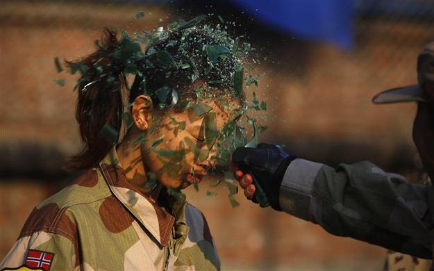 An instructor from the Tianjiao Special Guard-Security Consultant Ltd. Co, smashes a bottle over a female recruit's head during a training session for China's first female bodyguards in Beijing, January 13, 2012. REUTERS-David Gray