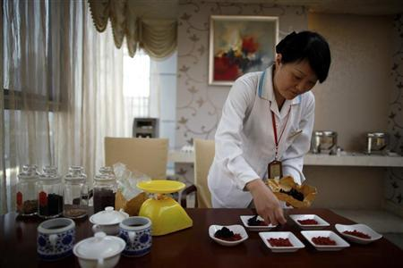 An employee prepares food for mothers using traditional Chinese medicine at the CareBay maternity care centre in Shanghai December 23, 2011.  REUTERS/Aly Song