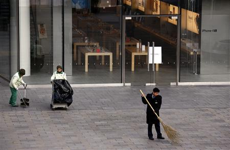 Cleaners clear rubbish in front of an Apple store with windows covered in egg in the Beijing district of Sanlitun January 13, 2012. REUTERS/David Gray