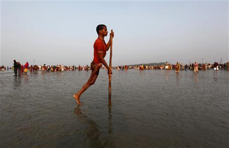 A polio affected man returns after taking a dip at the confluence of the Ganges river and the Bay of Bengal at Sagar Island, south of Kolkata, January 13, 2012. India is about to hit a milestone in its battle to eradicate the polio virus with no new cases reported in the past year, the country's health minister said on Thursday, a dramatic drop from being the country worst affected by the crippling disease. REUTERS/Rupak De Chowdhuri