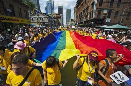 Revelers hold a giant pride flag as the take part in the Gay Pride Parade in Toronto, July, 3, 2011.  REUTERS/Mark Blinch