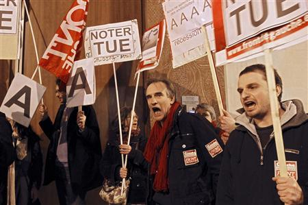 Demonstrators from the left-wing Parti de Gauche political party demonstrate outside the offices of Standard and Poor's in Paris, January 13, 2012. A euro zone official said that France and Austria would lose their top-notch triple-A ratings and Slovakia would also be affected in an announcement expected later today. Banners read  ''Notations Kill''.    REUTERS/Gonzalo Fuentes