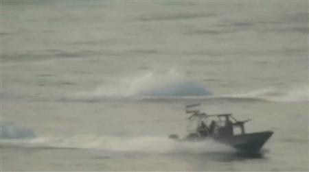 A small Iranian military motorboat with the Iranian national flag travels near the USS New Orleans in the Strait of Hormuz in this still image taken from January 6, 2012 video footage. Small Iranian military motorboats approached U.S. vessels passing through the Strait of Hormuz twice last week but the Pentagon said the interactions were not seen as hostile, even at a moment of heightened tensions between the two countries. The video released by the Pentagon showed armed boats with the Iranian Revolutionary Guard Corps' navy approaching within several hundred yards (metres) of the USS New Orleans, an amphibious transport ship, on January 6, a U.S. military official said. REUTERS/U.S. Department of Defense/Handout
