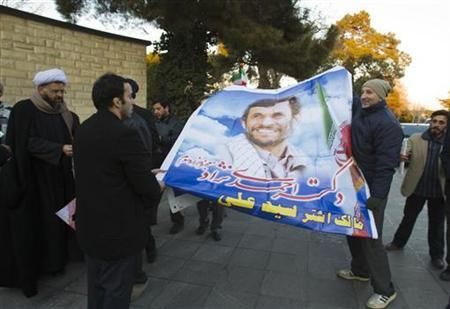 Supporters of Iranian President Mahmoud Ahmadinejad, hold a large poster of him as they wait for his arrival at Tehran's Mehrabad International Airport after his visit to Latin American countries January 14, 2012. REUTERS/Raheb Homavandi/EDITORS' NOTE: Reuters and other foreign media are subject to Iranian restrictions on their ability to film or take pictures in Tehran.
