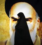 Женщина проходит мимо изображения Аятоллы Хомейни в Тегеране 3 июня 2011 года. Иран предостерег страны Персидского залива против повышения добычи нефти в случае введения международного эмбарго на импорт нефти из Ирана. REUTERS/Morteza Nikoubazl