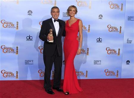 George Clooney and his girlfriend Stacy Keibler pose with his award for best actor in a motion picture - drama for 'The Descendants,' backstage at the 69th annual Golden Globe Awards in Beverly Hills, California, January 15, 2012. REUTERS/Lucy Nicholson