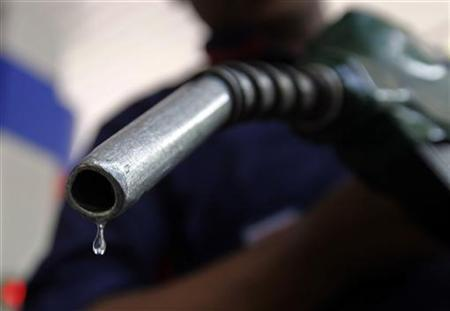 A worker holds a fuel nozzle at a petrol pump in Mumbai June 11, 2010. REUTERS/Danish Siddiqui/Files