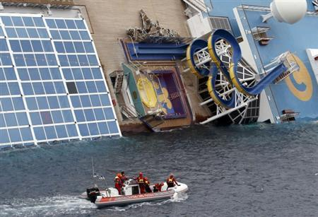 Rescue workers inspect the capsized Costa Concordia cruise ship that ran aground off the west coast of Italy at Giglio island January 16, 2012.  REUTERS/ Max Rossi